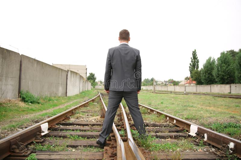Businessman standing on railway tracks. Concept of choice stock images