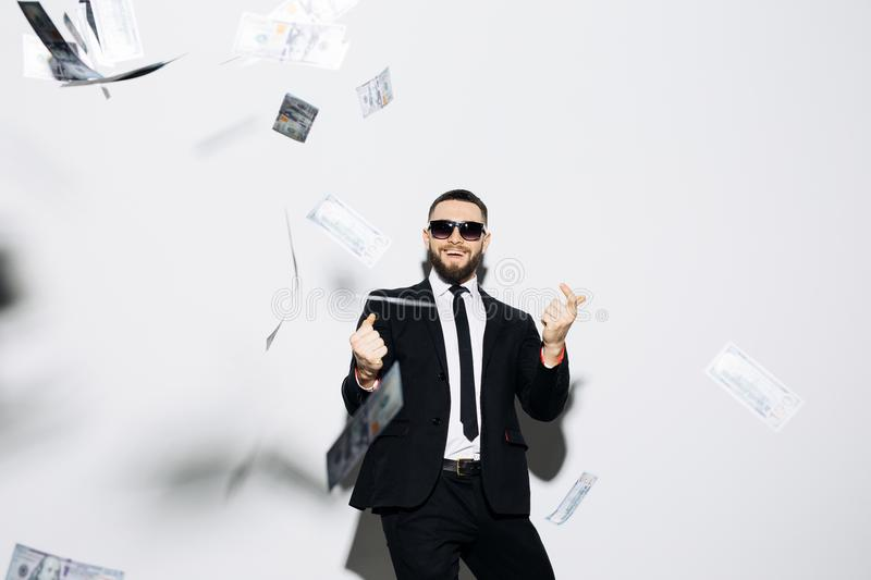 Handsome man in suit and sunglasses pointed up on fluy cash money on white background. Businessman standing in the rain of money. Businessman standing in the royalty free stock photo