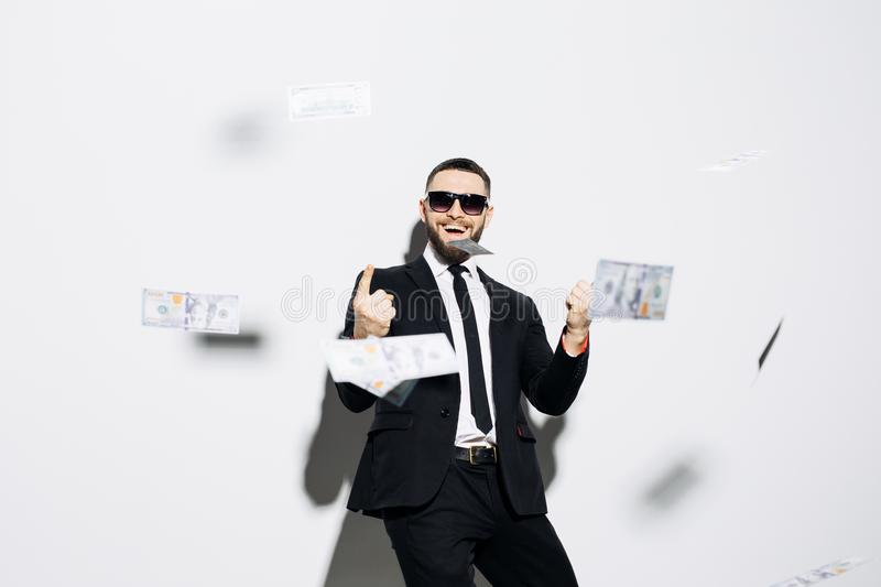 Handsome man in suit and sunglasses pointed up on fluy cash money on white background. Businessman standing in the rain of money. Businessman standing in the stock photo