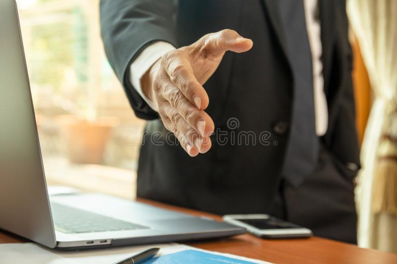Businessman standing and reaching out hand for shaking. royalty free stock photo