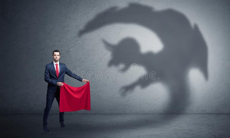 Businessman with imp shadow and toreador concept. Businessman standing with red cloth in his hand and imp shadow on the background royalty free stock image