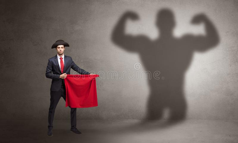 Businessman with strong hero shadow and toreador concept. Businessman standing with red cloth on his hand and strong hero shadow on the backgroundn royalty free stock photo