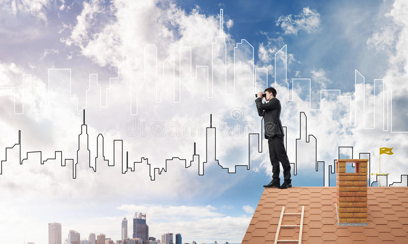 Businessman standing on roof and looking in binoculars. Mixed media. Young businessman viewing cityscape in his binoculars Mixed media stock image