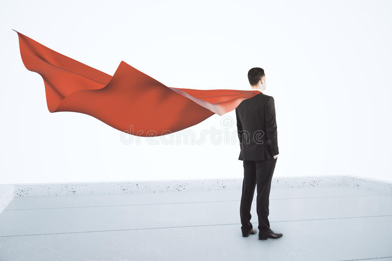 Businessman standing on the roof with a red cape, superhero concept royalty free stock photos