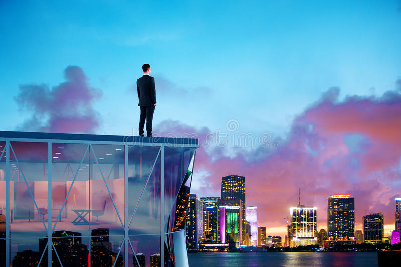 Businessman standing on the roof of a skyscraper and looking over the city at sunrise stock photo