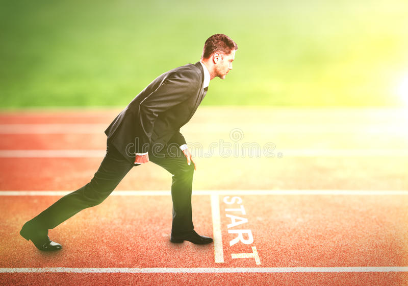 Businessman standing on running track stock image