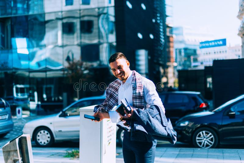 Businessman is standing on the street on a windy day and looking interested royalty free stock photo