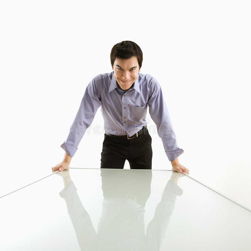 Businessman standing at table. Young Asian business man standing over conference table with devilish grin stock images