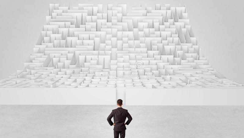 Small man standing in front of an infinity maze royalty free stock image
