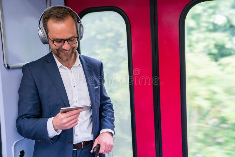 Businessman Standing On Train Streaming Movie From Mobile Phone To Wireless Headphones royalty free stock photos