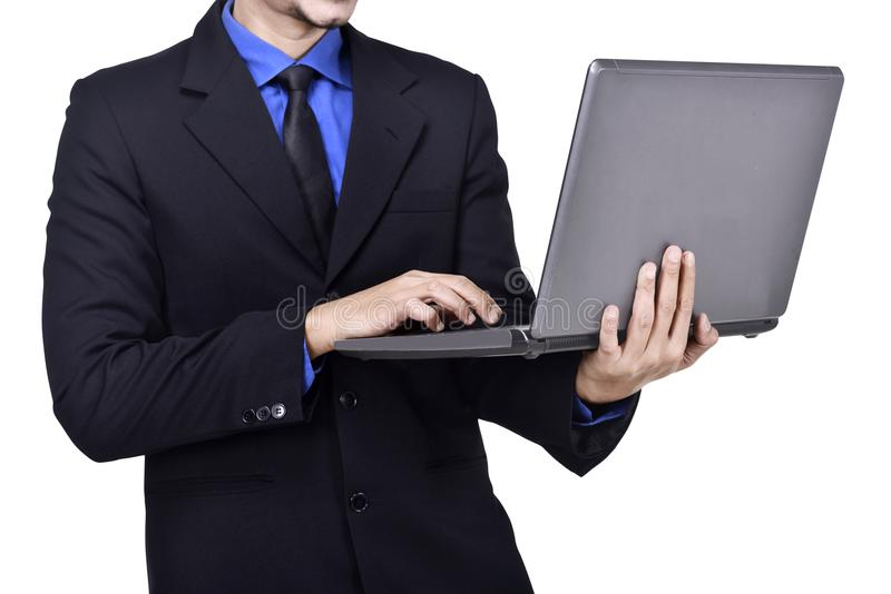 Businessman standing while typing on laptop royalty free stock images