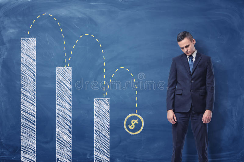 Businessman standing upset and column diagram with a dollar sign download businessman standing upset and column diagram with a dollar sign falling down stock image ccuart Images
