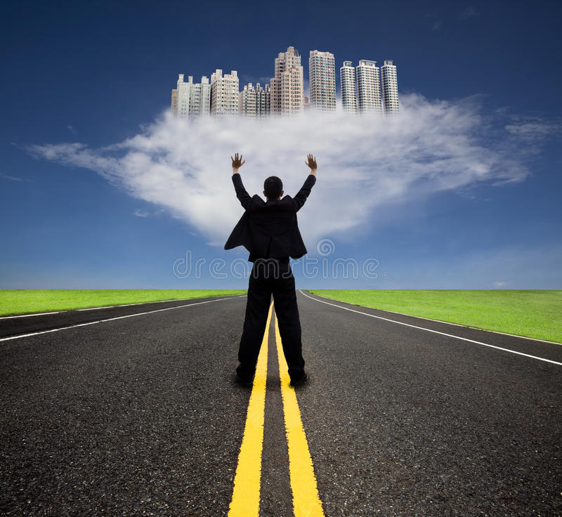 Businessman standing and watchin future city. Businessman standing on the empty road and watching the future city on the cloud royalty free stock image