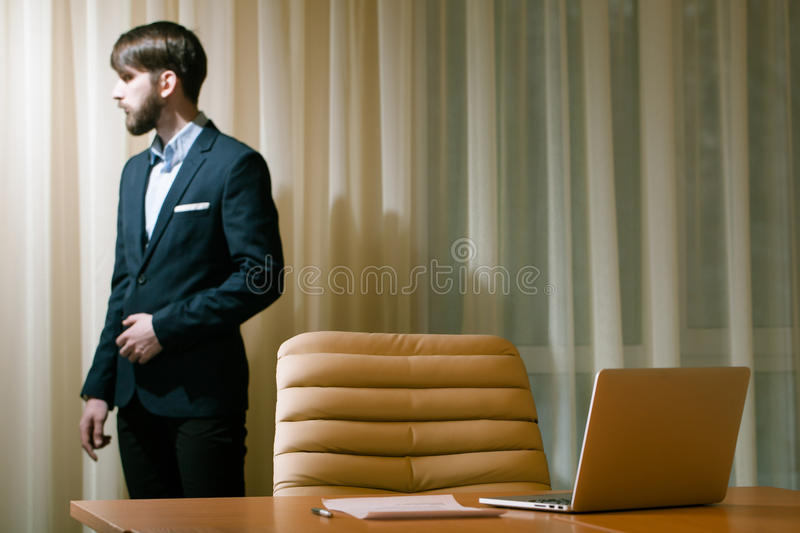 Businessman standing at window stock photos