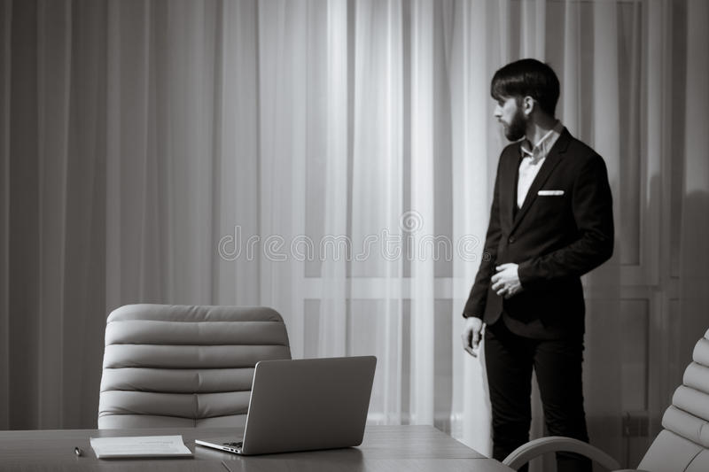 Businessman standing at window royalty free stock images