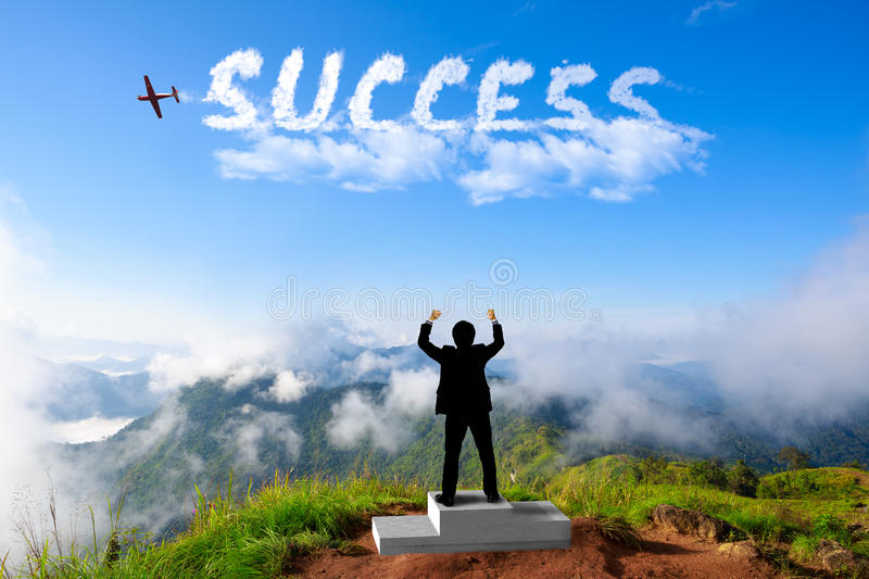 Businessman standing on a winner podium at the mountains. Success in business concept royalty free stock image
