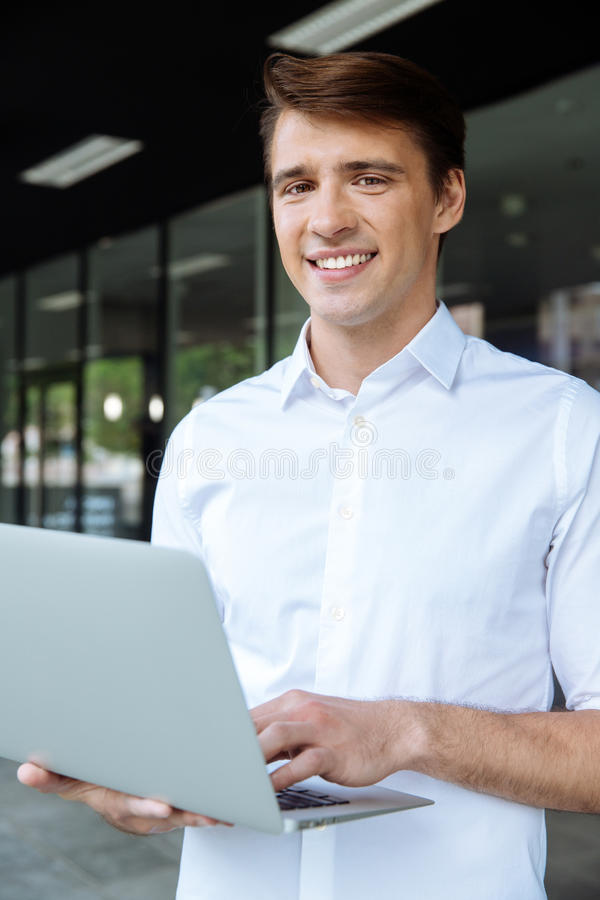 Businessman standing and working with laptop stock images