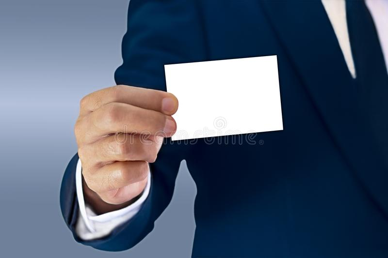 A businessman stands elegantly dressed in a blue suit and showing a business card held in hand. stock image