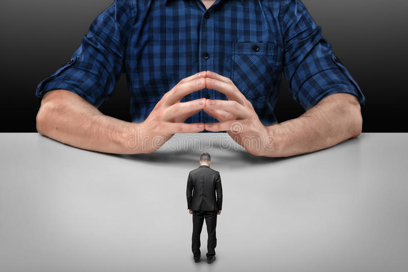 Businessman stands in front of big man sitting with his fingers clasped royalty free stock photo