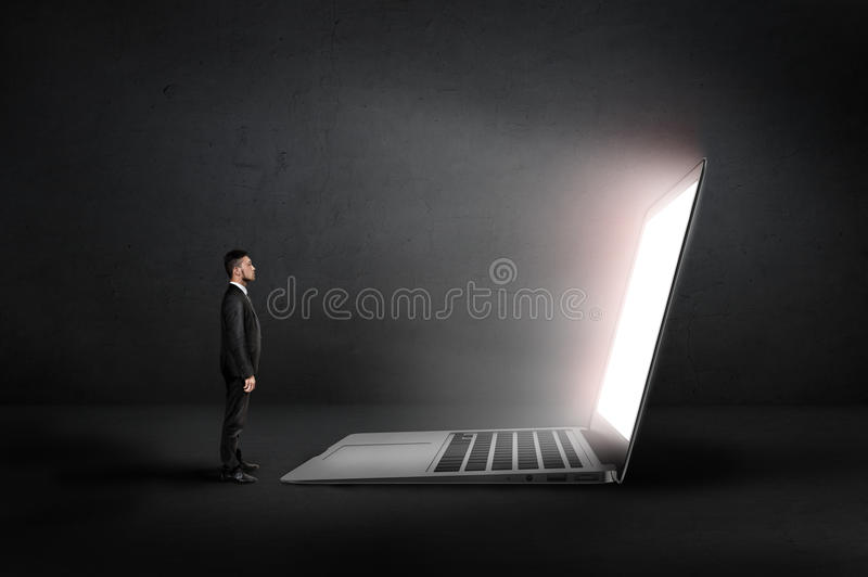 Businessman stands front of an open glowing huge laptop in the darkness. Profile view. A businessman stands in front of an open glowing huge laptop looking at royalty free illustration