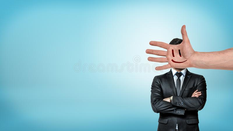A businessman stands in a front view with folded arms behind a giant male hand with a smiley face covering his head. Corporate rules. Work attitude. Boss and stock photos