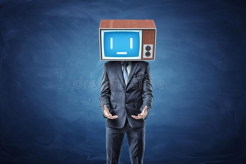 A businessman stands with his hands turned palms up in front of him and wears a sad TV screen on his head. Asking for help. In need of aid. Workplace support stock photo