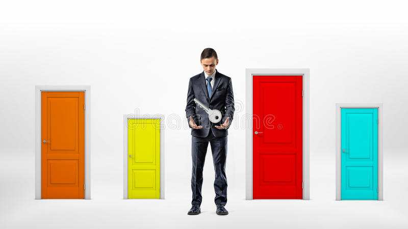 A businessman stands beside many small multicolored doors and looks at a large key hanging over his hands. stock photography