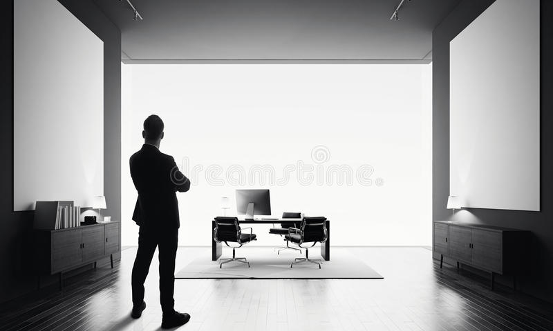 Businessman stands in modern office with two empty canvas. Black and white royalty free stock photos