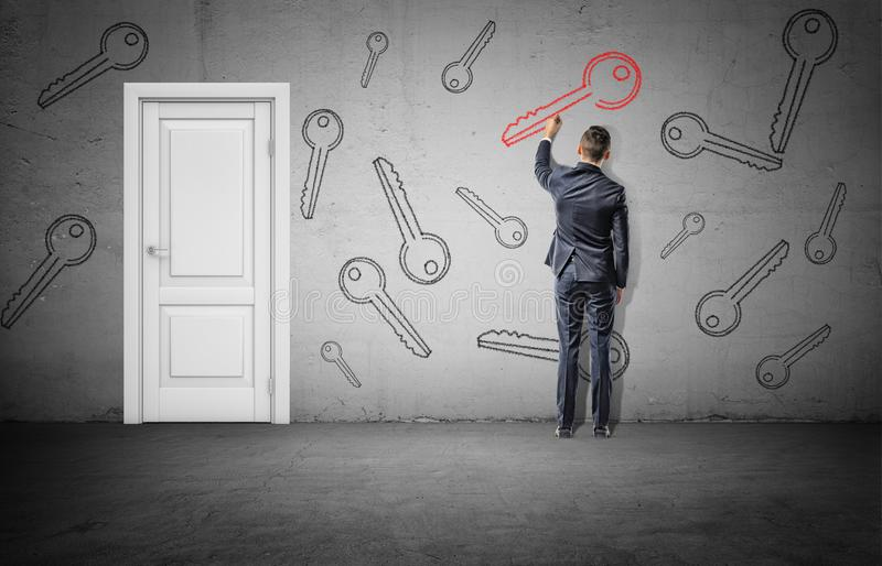 A businessman stands near a white closed door and draws a large red key on a wall beside many black keys. royalty free stock photo