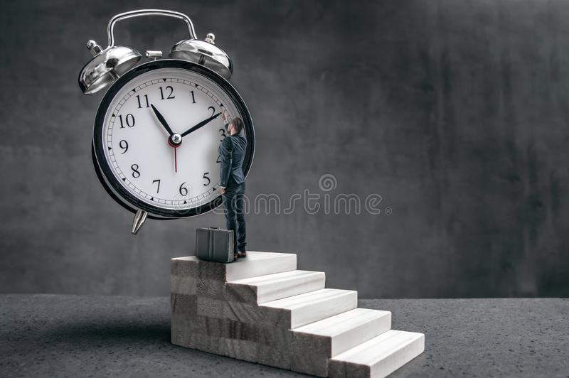 Businessman stands on stairs and tries to change clock hand stock photo
