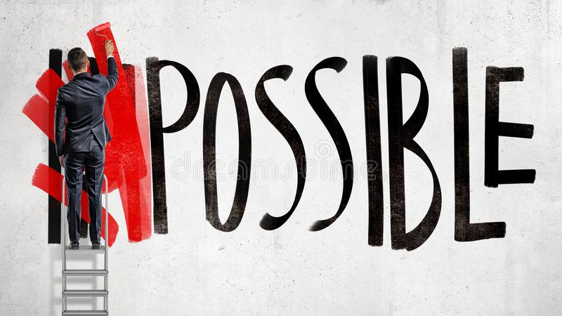 A businessman stands on a stepladder and hides the word Impossible written on the wall using a red paint roller. stock image