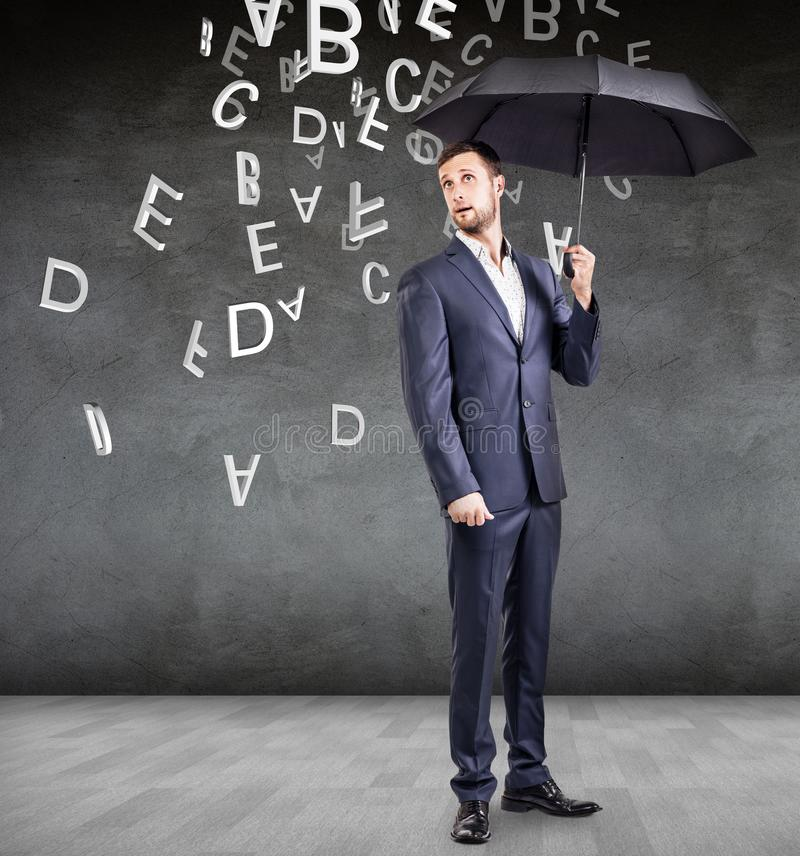 Businessman stands with umbrella under falling letters. stock photography