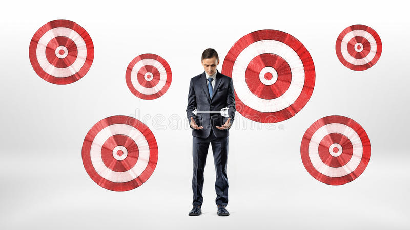 A businessman stands beside a wall with many archery targets and looks at an arrow hovering over his hands. stock photo