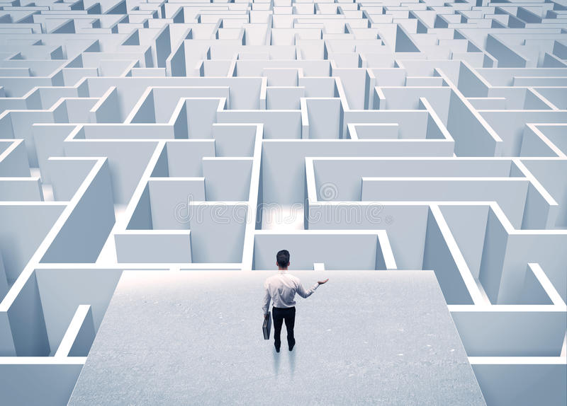 Businessman staring at infinite maze. An elegant businessman standing on a square platform looking over infinite labyrinth concept royalty free stock photos
