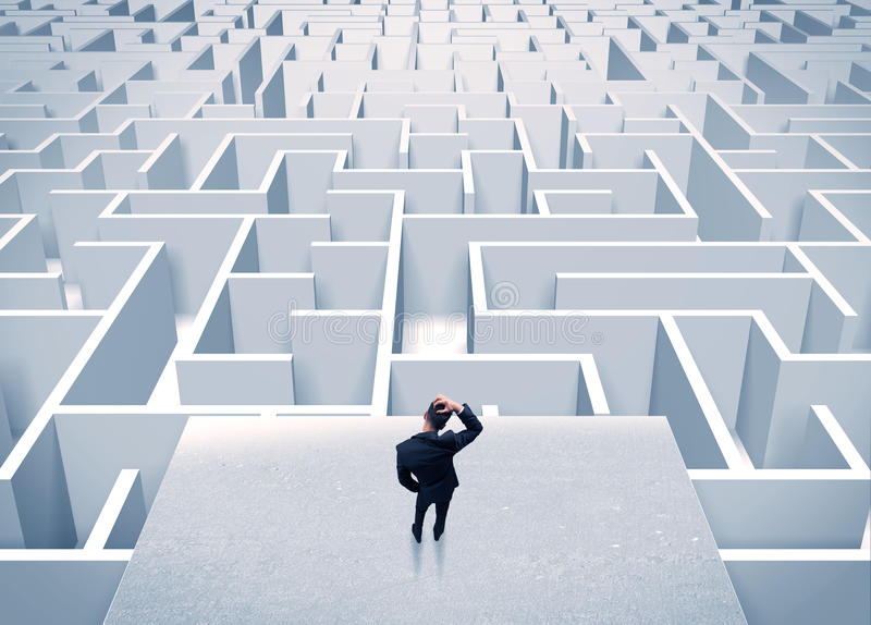 Businessman staring at infinite maze. An elegant businessman standing on a square platform looking over infinite labyrinth concept stock photos