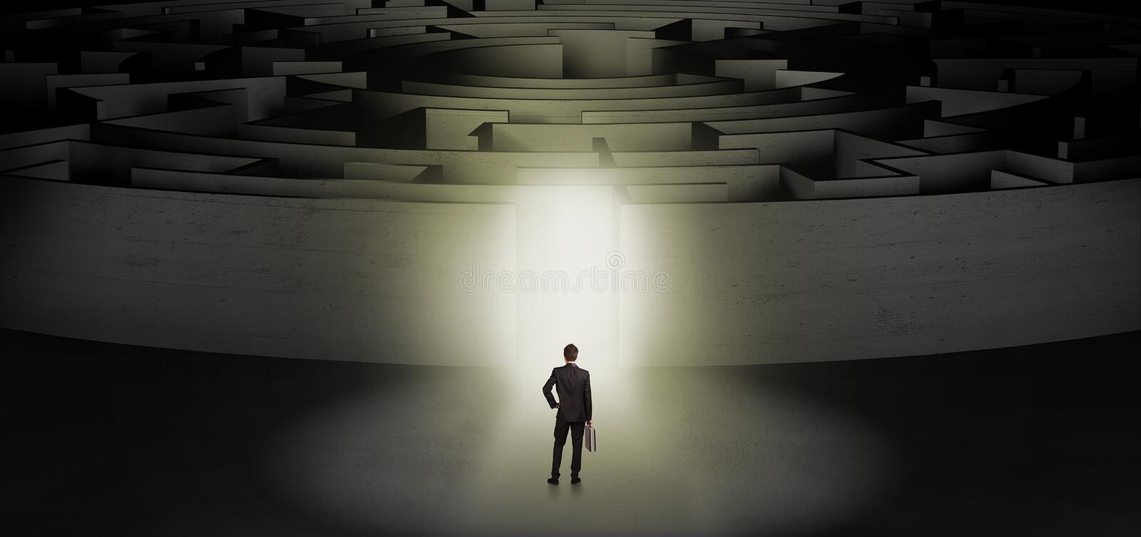 Businessman starting a concentric labyrinth. Businessman getting ready to enter a concentric labyrinth with lighted entrance concept royalty free stock photo