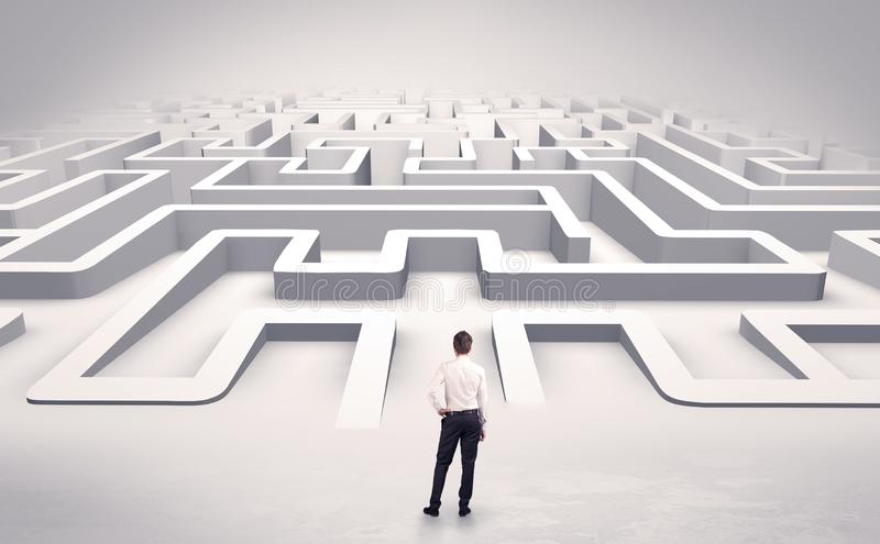 Businessman starting a flat 3d labyrinth. Businessman getting ready to enter a 3D flat labyrinth concept royalty free stock photo