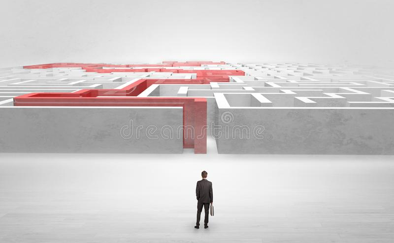 Businessman starting a stated labyrinth. Businessman getting ready to enter the labyrinth with stated road concept royalty free stock image