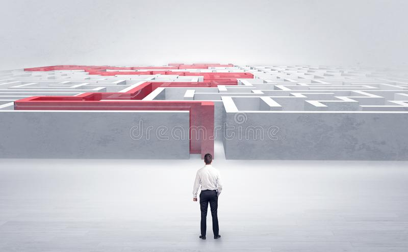 Businessman starting a stated labyrinth. Businessman getting ready to enter the labyrinth with stated road conceptn royalty free stock photos