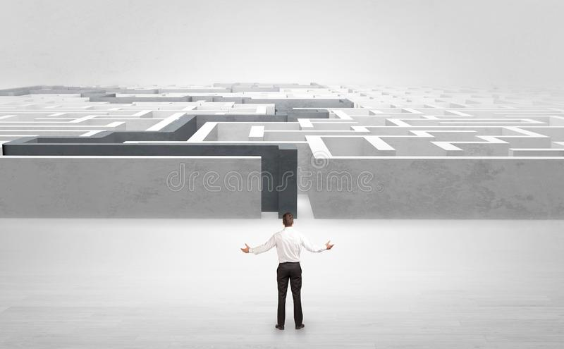 Businessman starting a stated labyrinth. Businessman getting ready to enter the labyrinth with stated road concept royalty free stock images