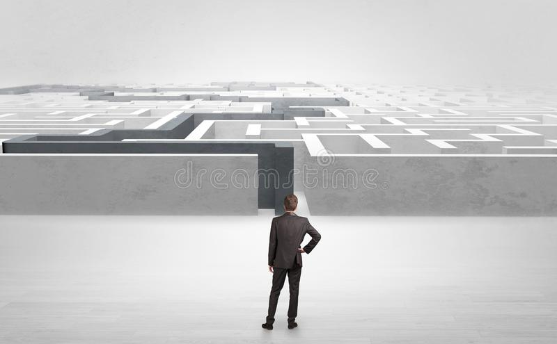 Businessman starting a stated labyrinth. Businessman getting ready to enter the labyrinth with stated road conceptn stock photo