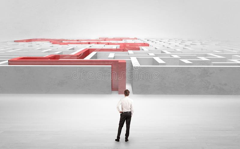 Businessman starting a stated labyrinth. Businessman getting ready to enter the labyrinth with stated road concept royalty free stock photo