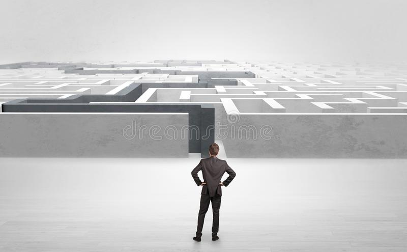 Businessman starting a stated labyrinth. Businessman getting ready to enter the labyrinth with stated road concept stock image