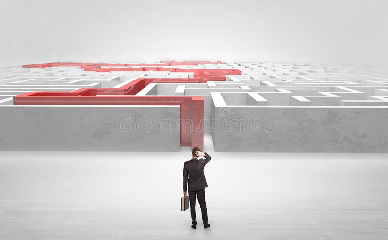 Businessman starting a stated labyrinth. Businessman getting ready to enter the labyrinth with stated road concept royalty free stock photos