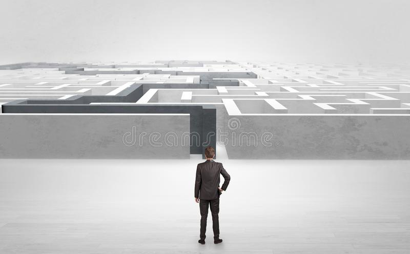 Businessman starting a stated labyrinth. Businessman getting ready to enter the labyrinth with stated road concept stock photography