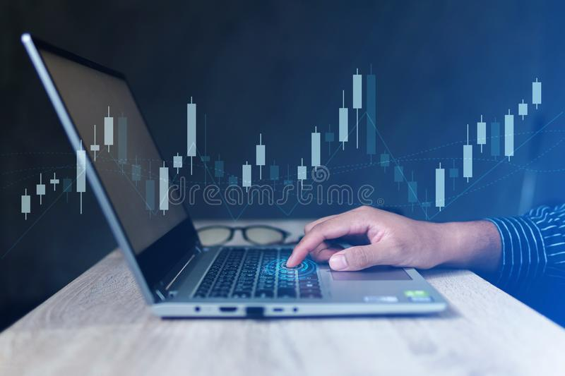 Businessman with statistic graph of stock market financial indices analysis on laptop screen stock image