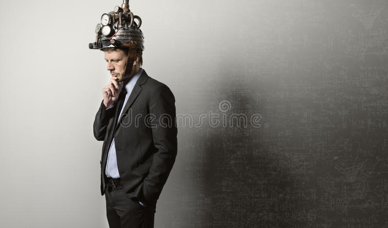 Businessman with steampunk helmet. Confident businessman thinking with hand on chin wearing steampunk helmet stock photography