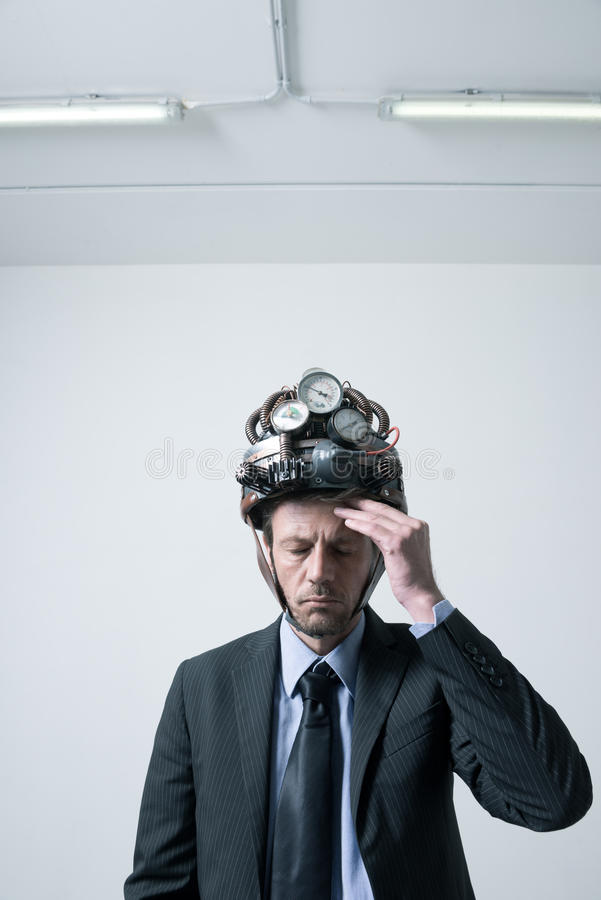 Businessman with steampunk helmet. Tired pensive businessman touching his forehead weaaring futuristic helmet with gauges royalty free stock images