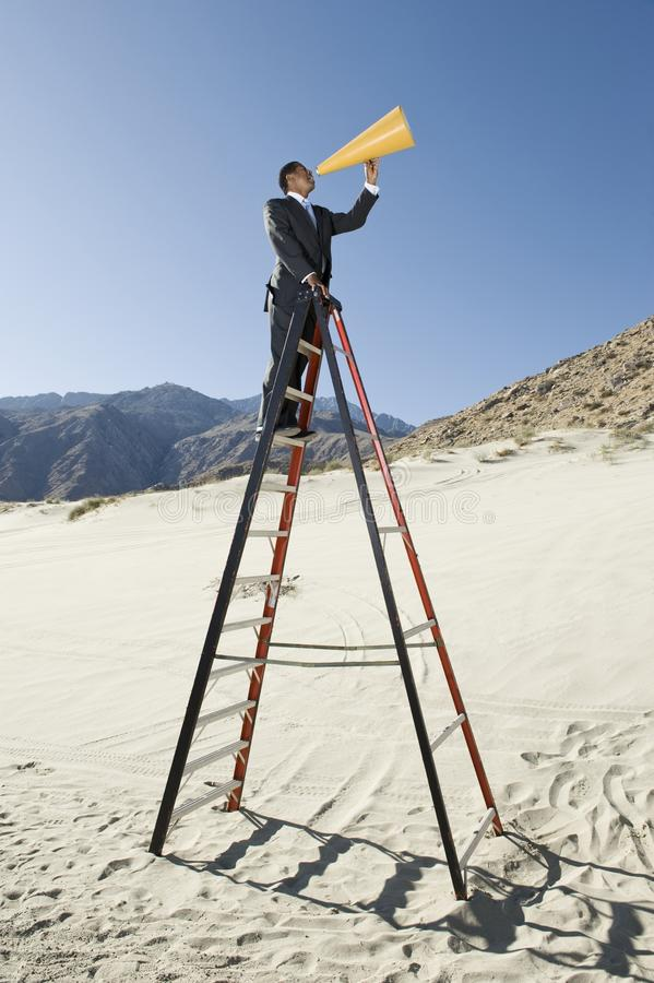 Businessman On Stepladder Using Megaphone In Desert. Side view of a businessman standing on stepladder using megaphone in desert royalty free stock images