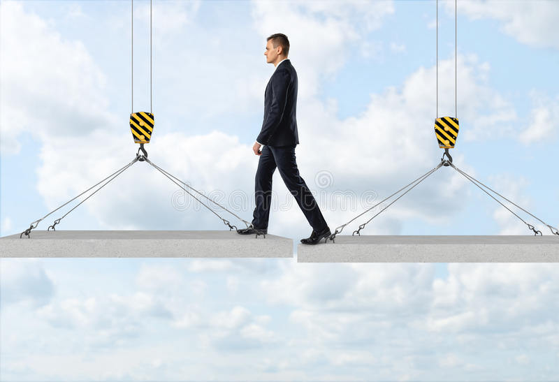 Businessman is stepping over a gap from one concrete panel to another in the air on the background of the sky. Goals and aspirations. Business activity. Risk stock image